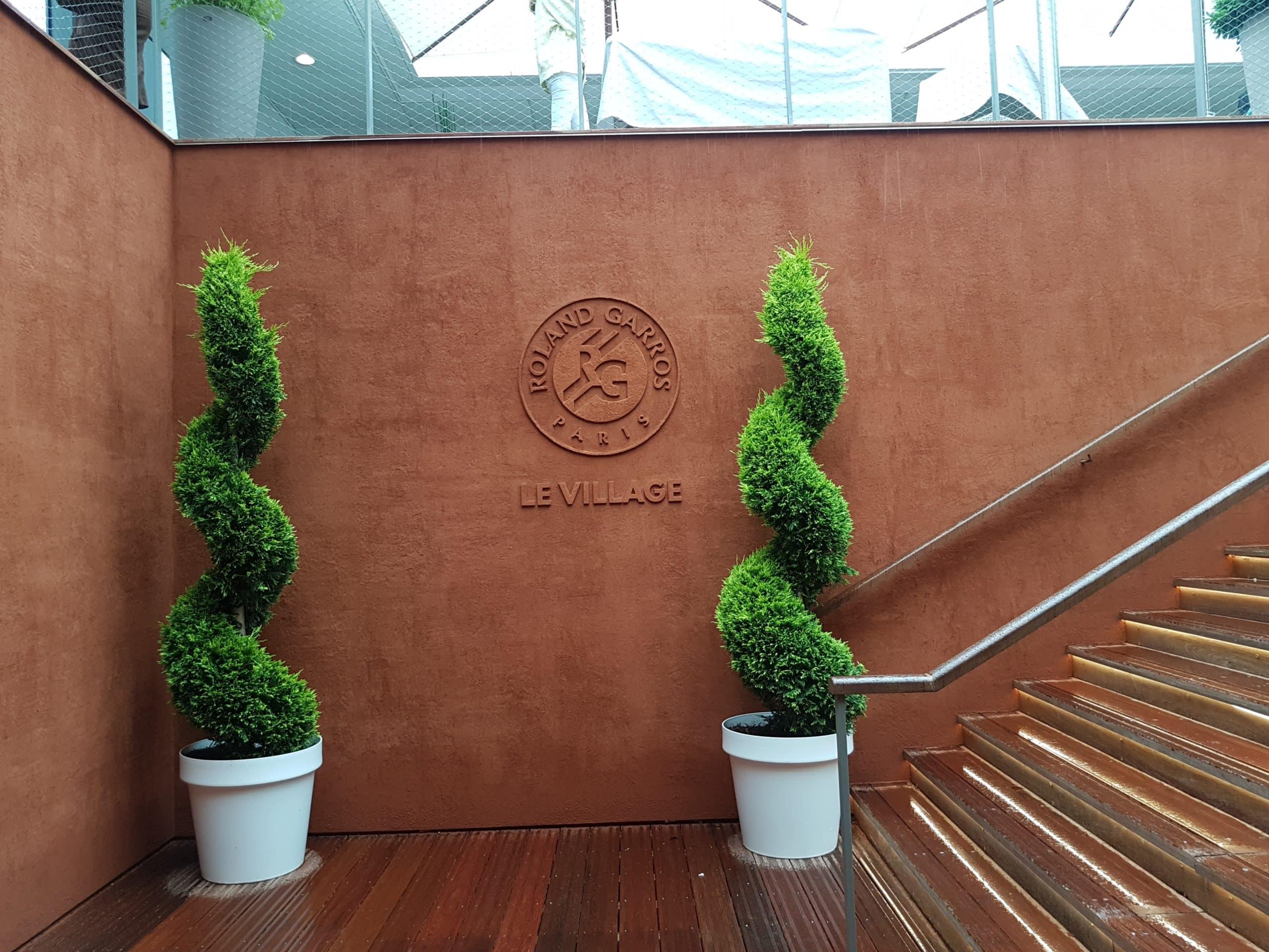 Entrée intérieure du Village entre le patio et le couloir muséal. Le logo de Roland-Garros est désormais embossée sur tous les supports : murs comme sièges.