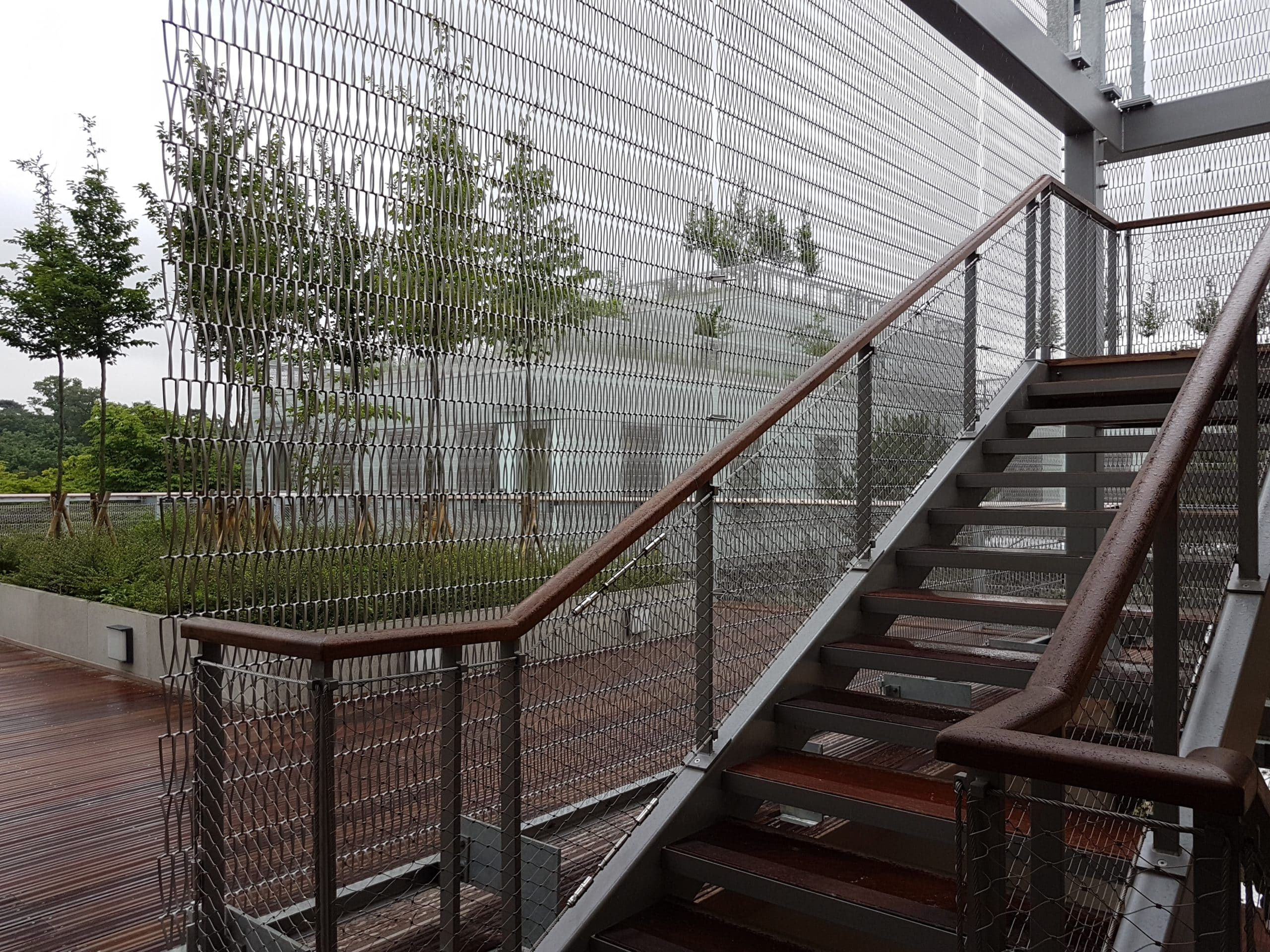 Les garde-corps des escaliers du village rappellent le cordage du filet de tennis quand la treille du bâtiment ouvre sur l'extérieur tout en protégeant des regards.
