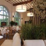"""Dans l'orangerie, les lustres sont rétractables pour une configuration """"conférence"""" et les fenêtres ont retrouvé le vert céladon des serres d'origine."""